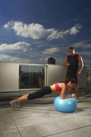 career timing: Woman exercising with trainer on rooftop