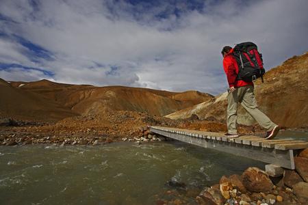 adventuresome: Hiker crossing wooden bridge