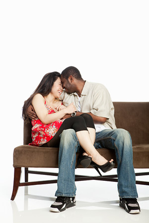Mixed race couple on sofa against white background LANG_EVOIMAGES