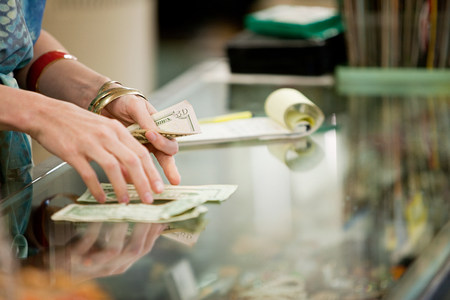 shop keeper: Shop keeper counting money in shop