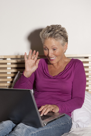 silver surfer: Older woman using laptop on bed