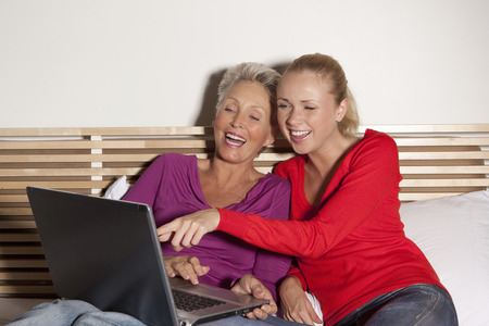 60 64 years: Mother and daughter using laptop