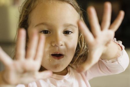 Close up of female toddler holding up hands LANG_EVOIMAGES