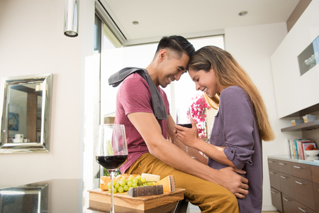 living room window: Loved up couple standing face to face in dining room