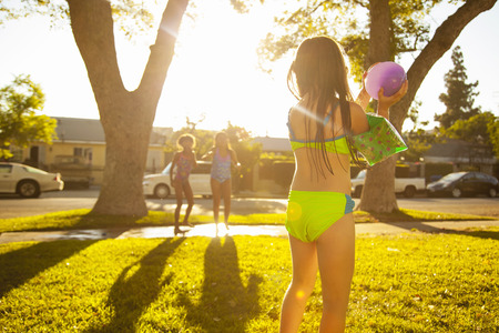 7 8: Girl chasing friends with water balloon in garden
