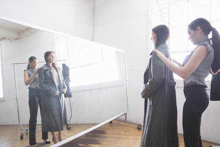 woman mirror: Businesswoman trying on coat