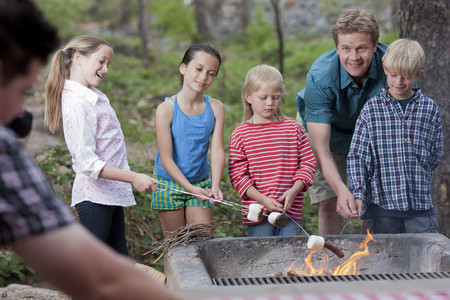 7 8: Mature couple and four children toasting marshmallows on campsite, Sedona, Arizona, USA LANG_EVOIMAGES