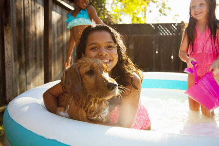 7 8: Three girls and a dog in garden paddling pool