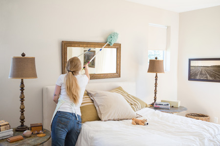 woman mirror: Young woman cleaning bedroom with green cleaning products LANG_EVOIMAGES