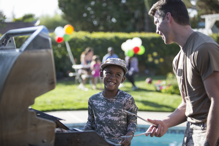 fatigues: Male soldier and boy barbecuing at homecoming party