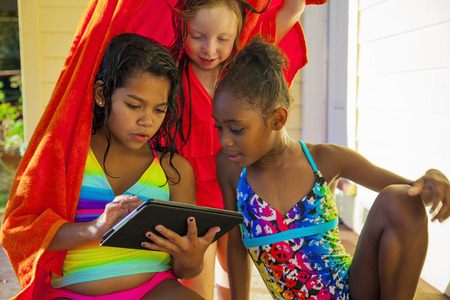 7 8: Three girls wrapped in towel on porch looking at digital tablet