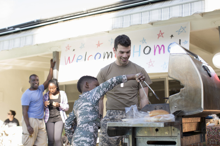 7 8: Boy barbecuing burgers with male soldier at homecoming party