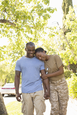 fatigues: Female soldier resting head on husbands shoulder whilst strolling on homecoming