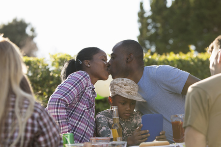 fatigues: Young couple kissing at soldiers homecoming party