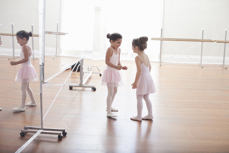 mirror image: Two child ballerinas chatting in ballet school LANG_EVOIMAGES