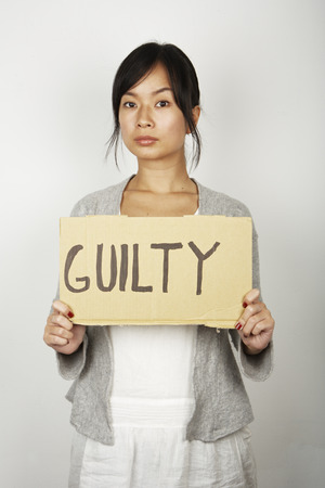 questions: Studio portrait of mid adult woman holding up guilty sign LANG_EVOIMAGES