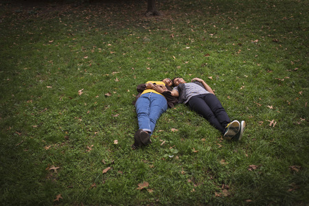 50 54 years: Two mature female friends lying on park grass head to head