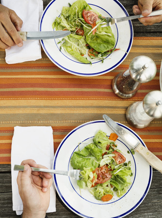 60 64 years: Overhead of the hands of father and son eating salad at table