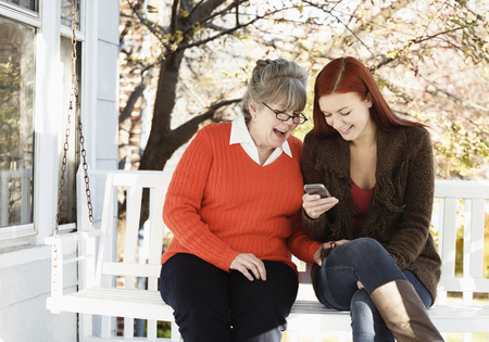 60 64 years: Senior woman and adult daughter reading phone texts on porch