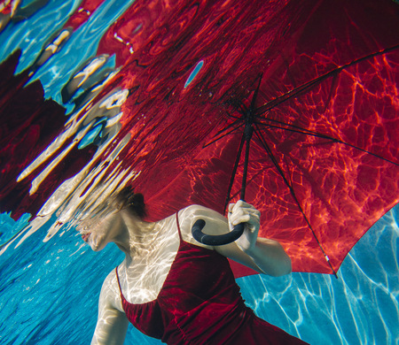 out of context: Mature woman wearing red dress, holding red umbrella, underwater view, mid section LANG_EVOIMAGES