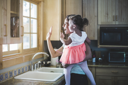 sink: Mother and daughter playing in kitchen
