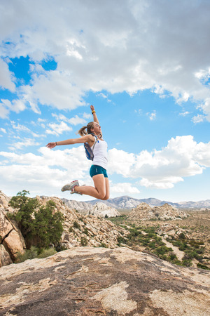 joshua tree national park: Woman jumping for joy on mountain, Joshua Tree National Park, California, US