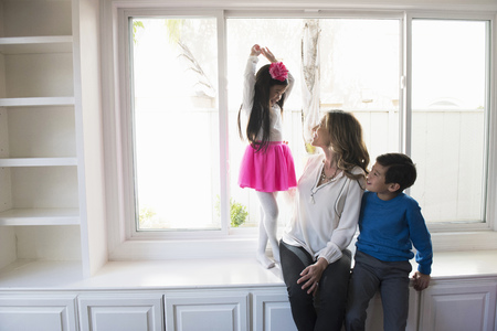 living room window: Mature woman and son looking up at girl dancing LANG_EVOIMAGES