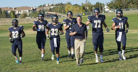 numeric: Teenage and young adult american football  training with coach