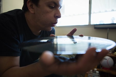 living room window: Close up of young man blowing surface of vinyl record