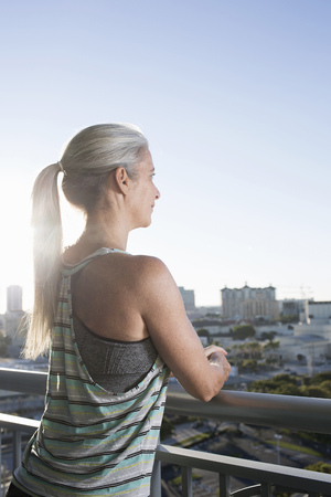 50 54 years: Mature woman in sports clothing leaning against city balcony