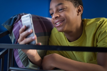 bunkbed: Close up of teenage boy lying in bunkbed reading smartphone text