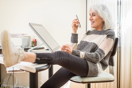 silver surfer: Portrait of senior woman sitting at computer holding smartphone with foot on desk LANG_EVOIMAGES