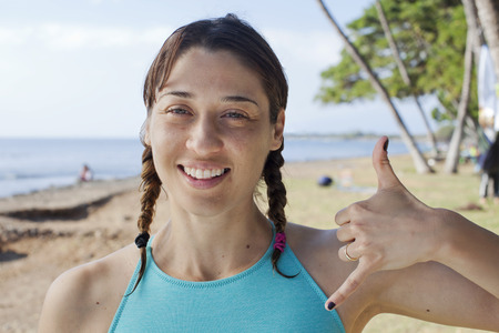 Woman making hand gesture on beach LANG_EVOIMAGES