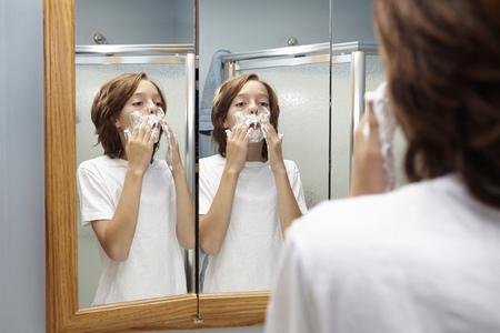 mirror image: Boy practicing applying shaving foam in bathroom mirror