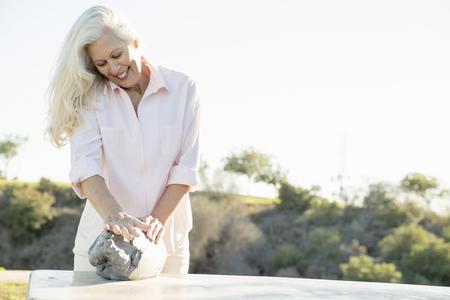 60 64 years: Senior woman making pottery, Hahn Park, Los Angeles, California, USA