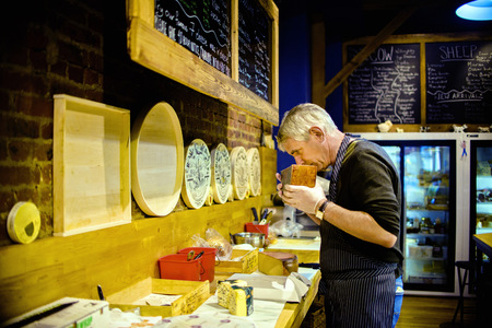 shop keeper: Cheesemonger smelling cheese