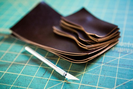 rectangle: Stack of cut leather pieces and scalpel on cutting mat LANG_EVOIMAGES