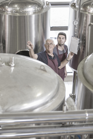near beer: Brewers in brewery next to stainless steel tanks