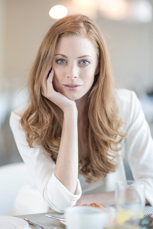 Portrait of young businesswoman breakfasting in hotel restaurant