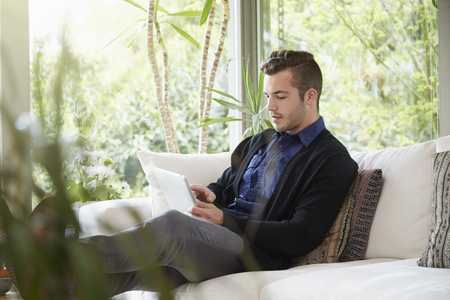 living room window: Man relaxing on sofa with feet up looking at digital tablet