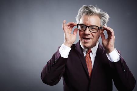 insincere: Studio portrait of mature businessman adjusting his spectacles