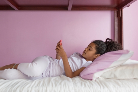 7 8: Side view of girl wearing pyjamas lying on bed looking at smartphone