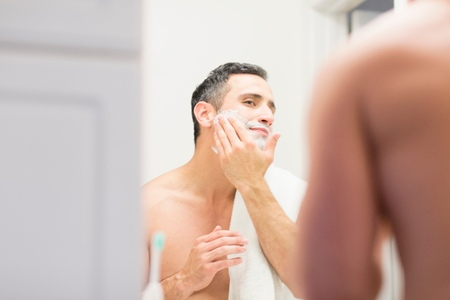 bathroom interior: Mid adult man, looking in mirror, applying shaving foam to face, rear view LANG_EVOIMAGES