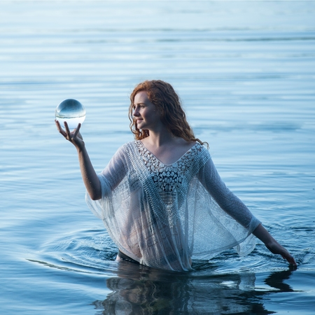 Young woman standing in lake gazing at crystal ball LANG_EVOIMAGES