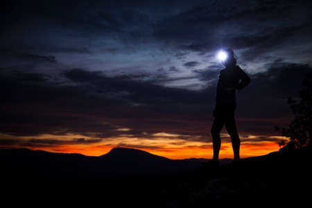 high sierra: Young woman standing at nights in darkness wearing headlamp