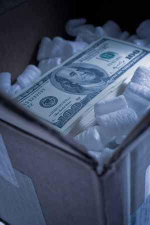 numeric: Stack of one hundred dollar bill in cardboard box with foam packing peanuts