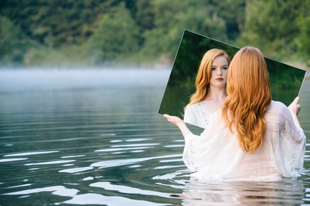mirror image: Rear view of young woman standing in lake holding mirror looking at reflection