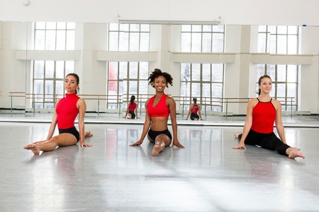 woman mirror: Front view of young women in dance studio side by side  doing the splits