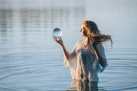 Young woman with long red hair standing in lake gazing at crystal ball