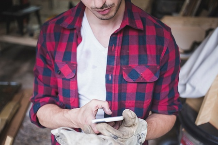 world at your fingertips: Cropped view of young mans hands wearing protective gloves using smartphone